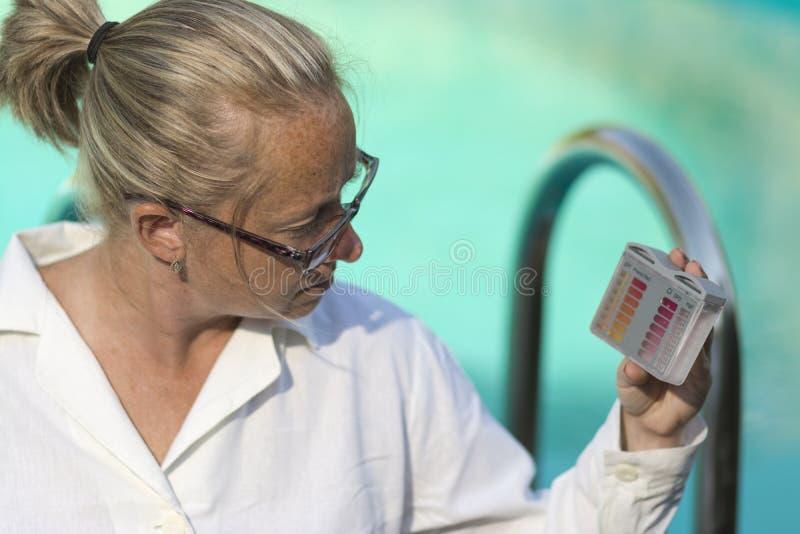 Het meisje controleert de PH en Chloorniveaus gebruikend een test op de achtergrond van de pool stock foto