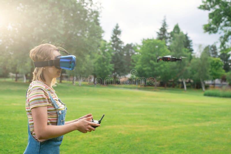 Het meisje controleert een quadrocopter in het park met behulp van een VR-helm Het concept virtuele werkelijkheid extra werkelijk stock afbeelding