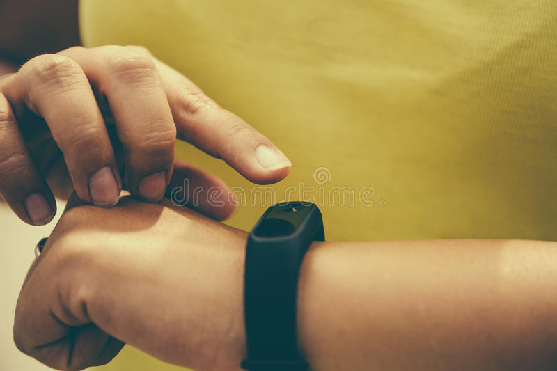 Het meisje controleert impuls op fitness armband of de pedometer van de activiteitendrijver op pols, sport, technologie en gezond stock afbeeldingen