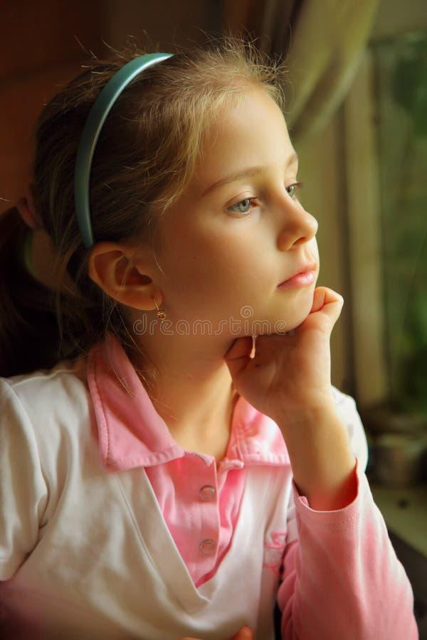 Het meisje dat bij een venster droomt stock afbeelding