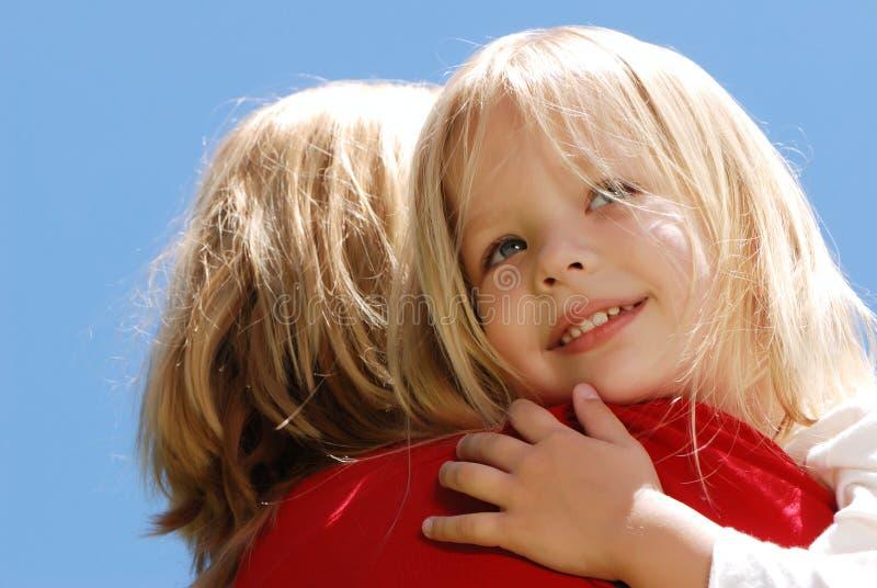 Het meisje dat de moeder omhelst tegen de hemel royalty-vrije stock afbeeldingen