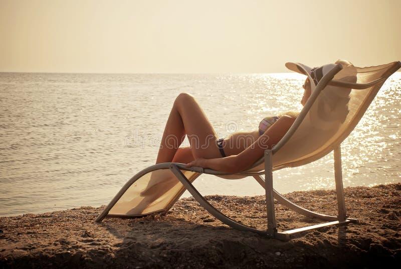 Het meisje dat een rust op zeekust heeft royalty-vrije stock foto's