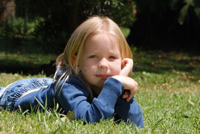 Het meisje dat op een gras legt royalty-vrije stock fotografie