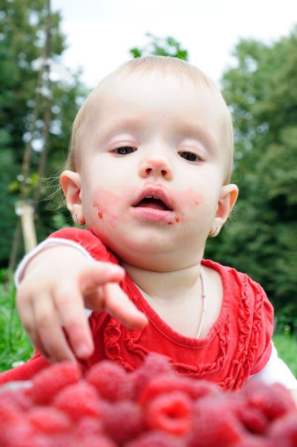 Het meisje dat van éénjarigen frambozen eet stock fotografie