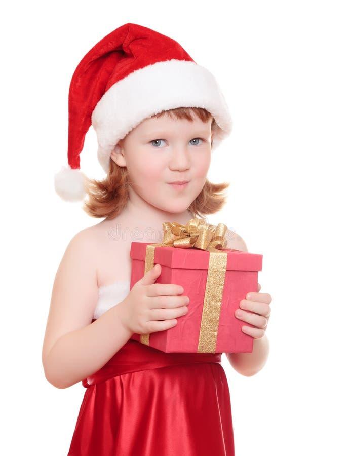 Het meisje dat van de baby in de hoed van de Kerstman haar huidig houdt stock fotografie