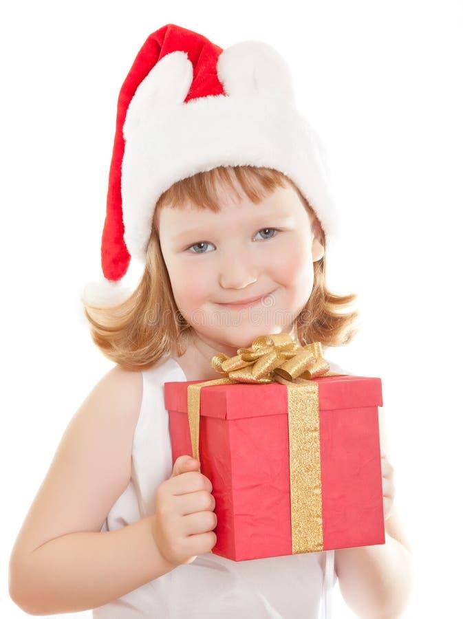 Het meisje dat van de baby in de hoed van de Kerstman haar huidig houdt royalty-vrije stock fotografie