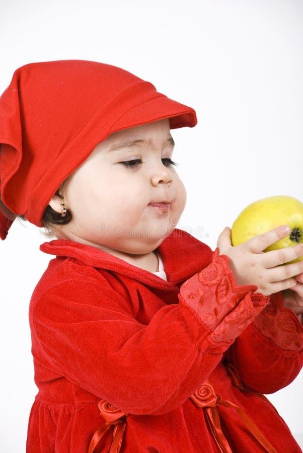 Het meisje dat van de baby een appel houdt stock afbeelding
