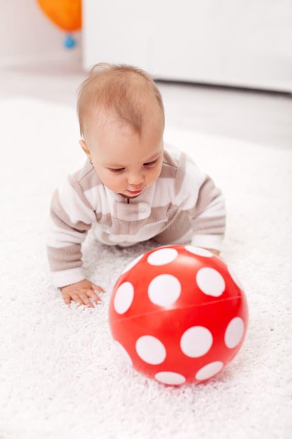 Het meisje dat van de baby een rode bal achtervolgt royalty-vrije stock foto's