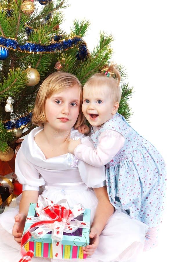 Het meisje dat van de baby haar zuster koestert onder Kerstmis t stock fotografie