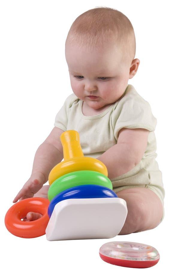 Het meisje dat van de baby het stapelen van ringen bekijkt. royalty-vrije stock fotografie
