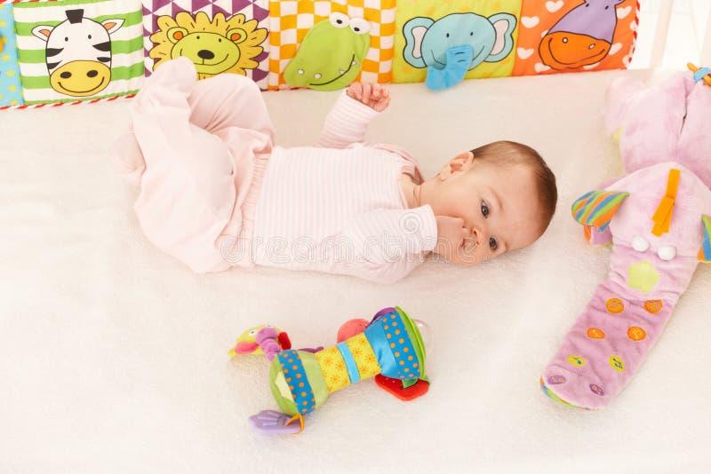 Het meisje dat van de baby kleurrijk stuk speelgoed bekijkt stock fotografie