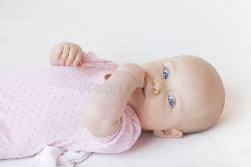 Het meisje dat van de baby op bed ligt stock foto's