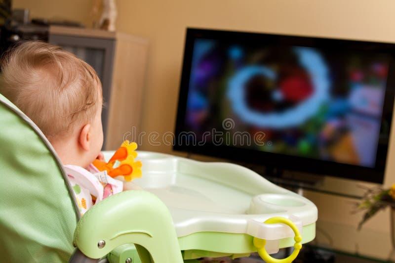 Het meisje dat van de baby op TV let stock afbeeldingen