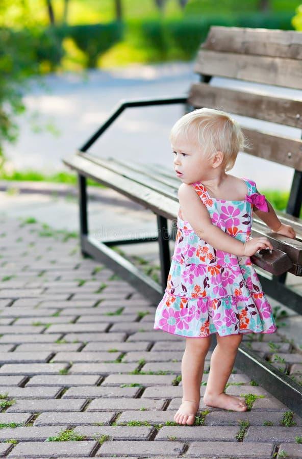 Het meisje dat van de baby zich dichtbij bank bevindt royalty-vrije stock afbeelding