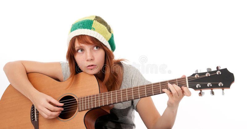 Het meisje dat van de tiener een akoestische gitaar speelt stock afbeelding