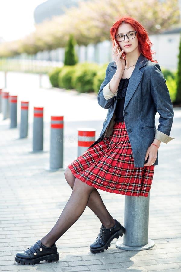 Het meisje dat van de tiener op de telefoon spreekt Rood Haar Concept levensstijl, stedelijk, Internet, sociale netwerk en studie royalty-vrije stock foto
