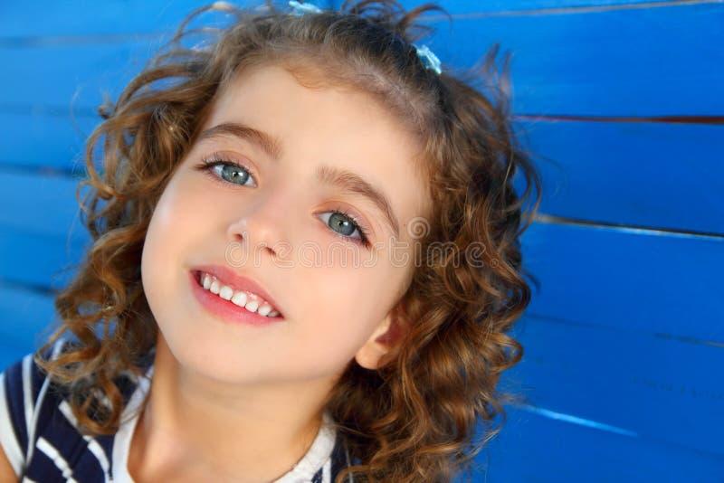 Het meisje dat van kinderen op houten blauwe muur glimlacht stock fotografie
