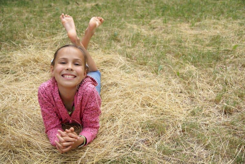 Het meisje dat van Preteen op hooi rust royalty-vrije stock foto
