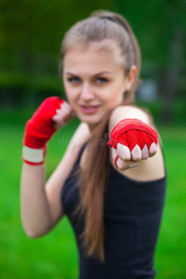 Het meisje de atleet, de bokser, in het park geeft ook de hand in een vuist met de gewonden sporten, rood verband vooruit wordt s stock fotografie