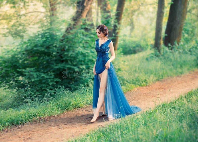 Het meisje in de avond, luxueus, waterverfkleding, met een hoge spleet Lange benen Het beeld van de partij, jongelui royalty-vrije stock foto