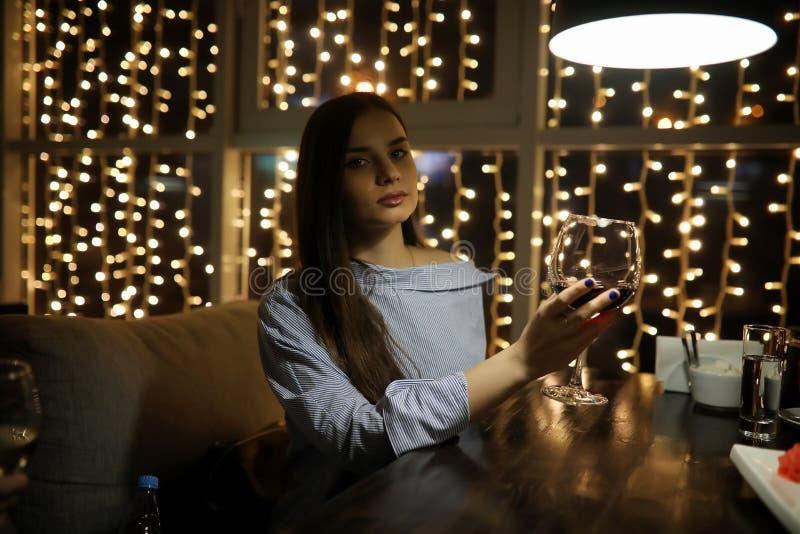 Het meisje in de avond rest in een koffie stock afbeeldingen