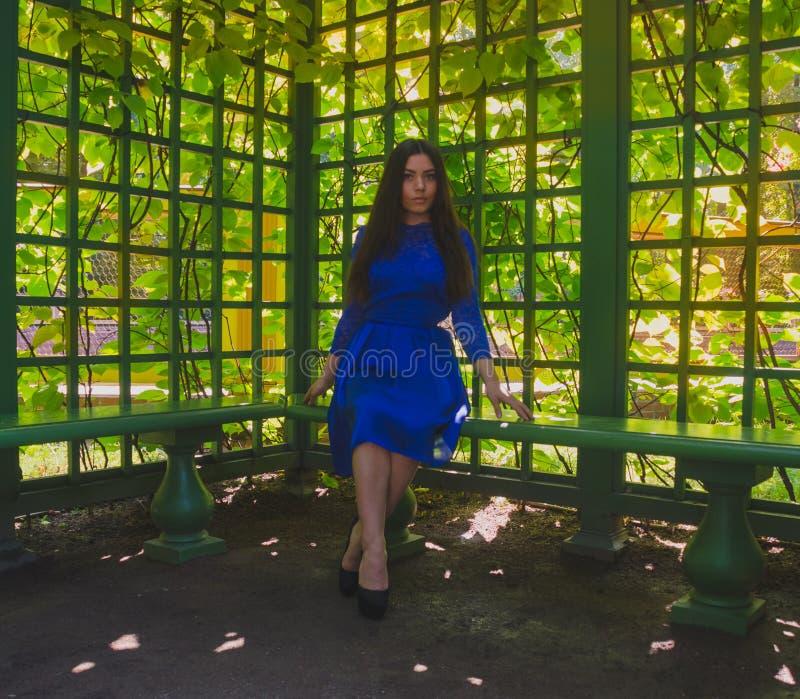 Het meisje in de blauwe kleding heeft een rust in gazebo royalty-vrije stock afbeelding
