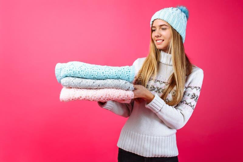 Het meisje in de blauwe warme hoed, die sjaals op een rode backgrou houden royalty-vrije stock afbeelding
