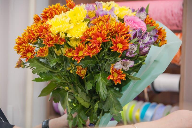 Het meisje de bloemist maakt een boeket van bloemen De bloemist doet een boeket stock afbeelding