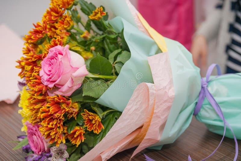 Het meisje de bloemist maakt een boeket van bloemen De bloemist doet een boeket royalty-vrije stock foto's