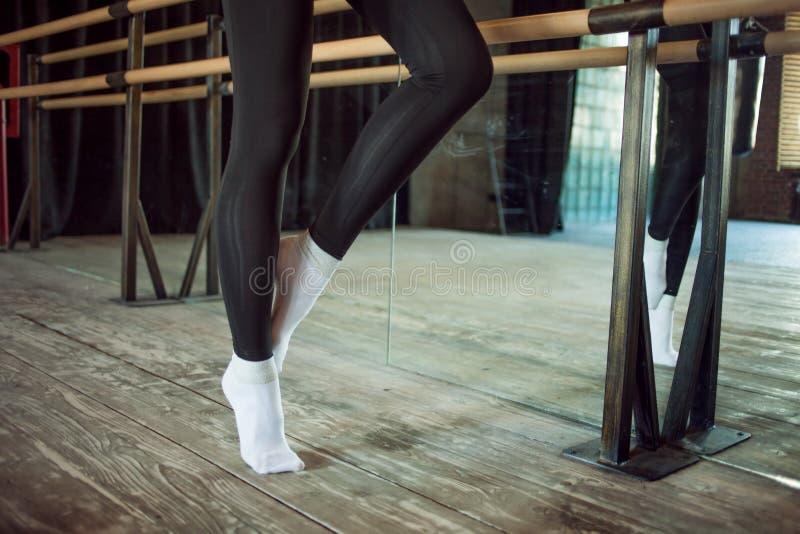Het meisje de danser naast een balletbar, Benen sluit omhoog stock foto