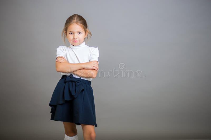 Het meisje de eerste nivelleermachine in een eenvormige school - een rok en een witte blouse stellen op een grijze achtergrond stock foto