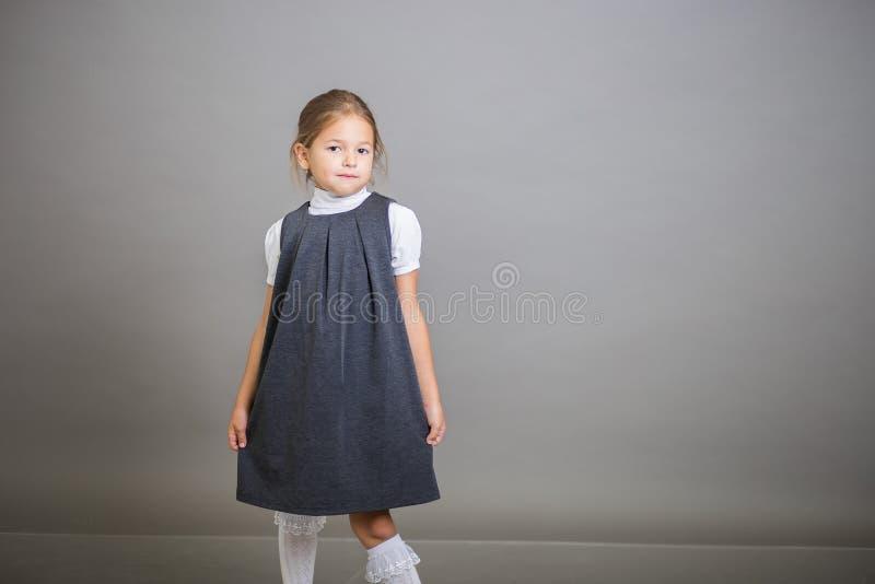 Het meisje de eerste nivelleermachine in een eenvormige school - stellen grijze sundress en een witte blouse op een grijze achter royalty-vrije stock foto's