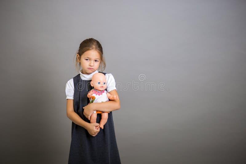 Het meisje de eerste nivelleermachine omhelst een pop en snakt dat het noodzakelijk om naar school is te gaan stock fotografie