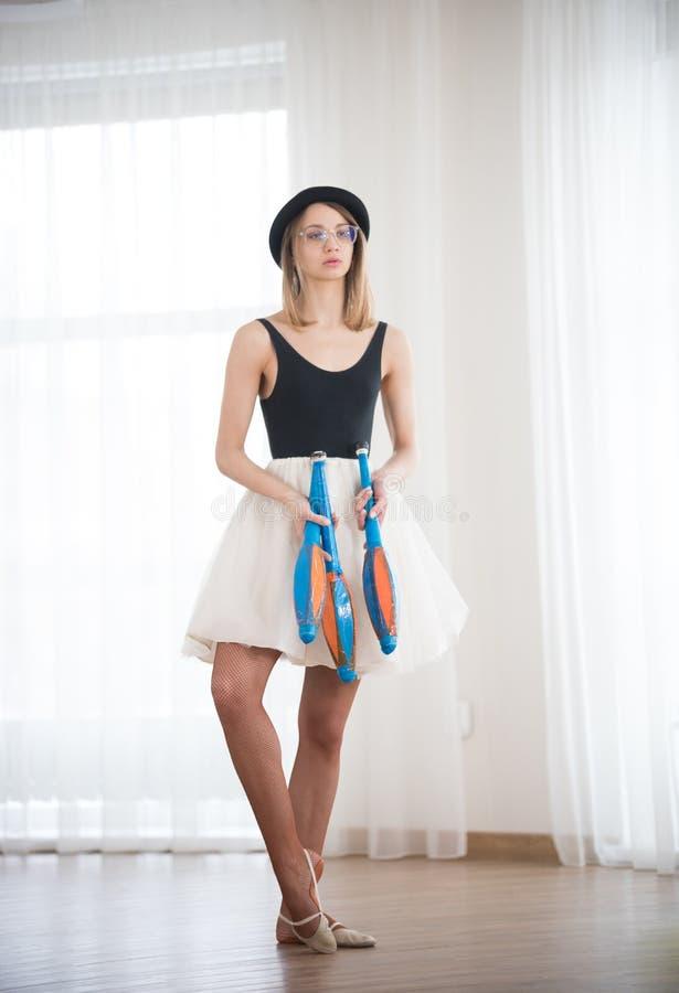 Het meisje in de hoed houdt in haar handen de het jongleren met spelden, in de studio stock fotografie