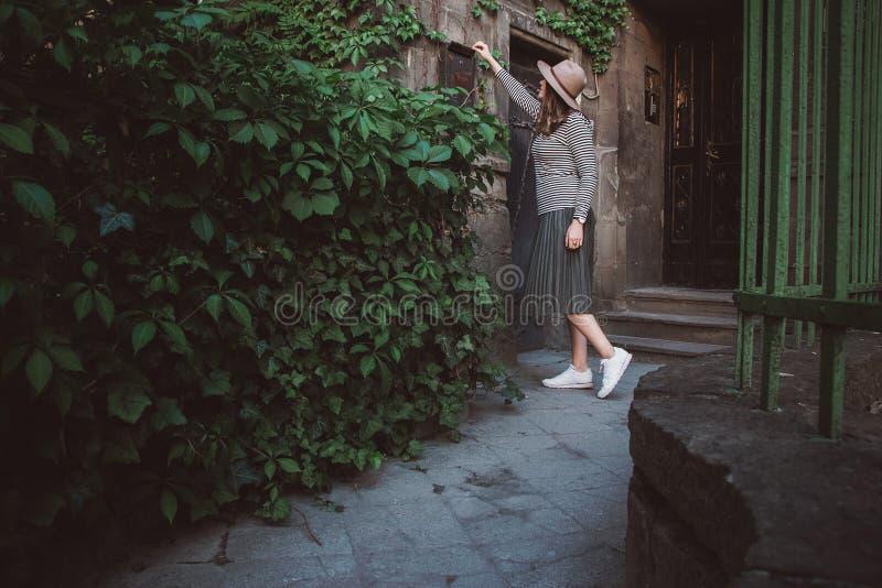 Het meisje in de hoed opent een brievenbus met bladen bij de achtergrond van het oude huis stock fotografie