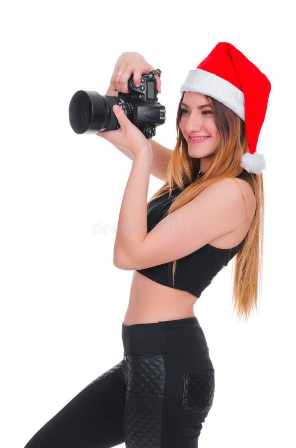Het meisje in de hoed van Santa Claus met een camera Jonge meisjesfotograaf Christmas Kerstmis selfie stock foto