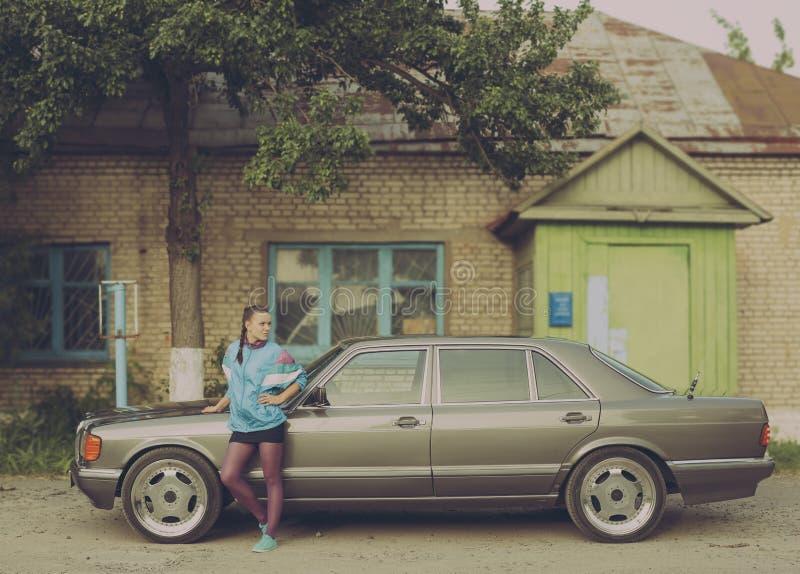 Het meisje in de jaren '90 is over auto's royalty-vrije stock afbeeldingen