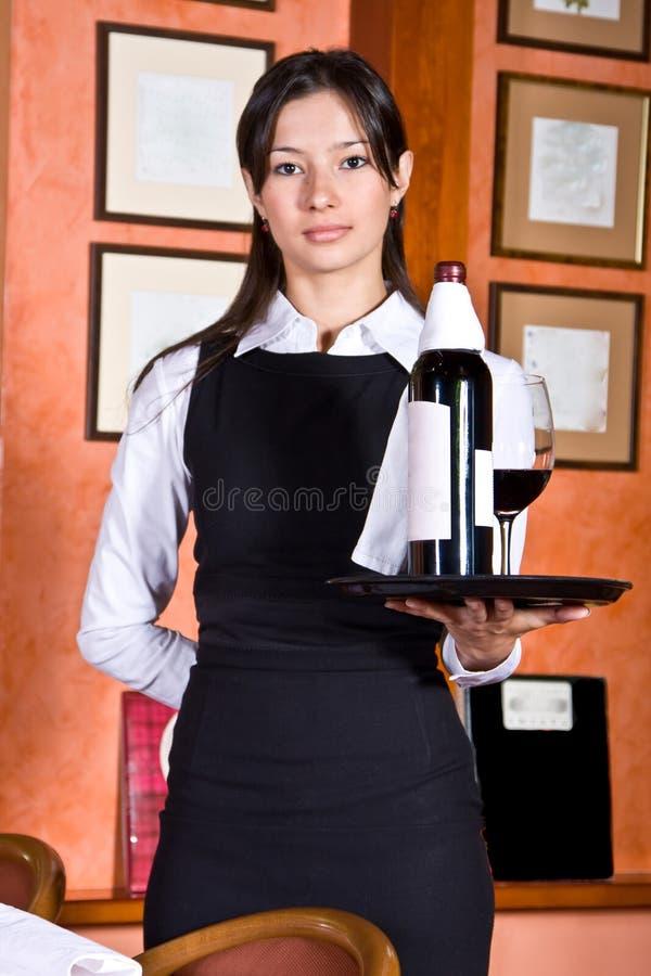 Het meisje de kelner met een dienblad met wijn royalty-vrije stock afbeelding