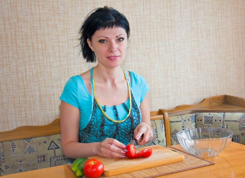 Het meisje in de keuken sneed de groenten royalty-vrije stock afbeeldingen