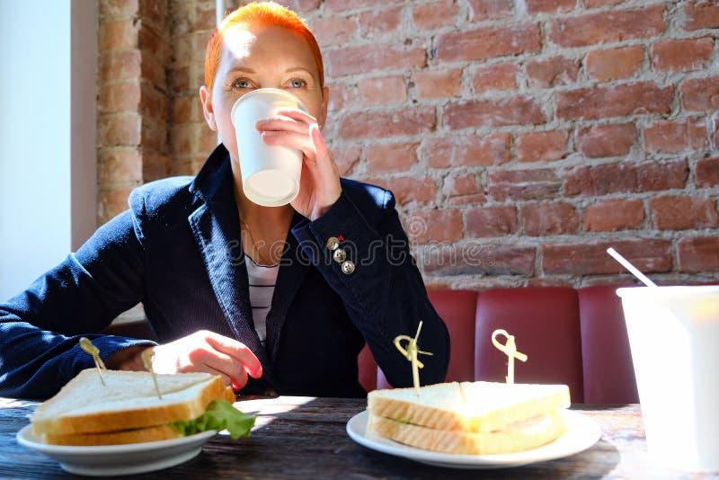 Het meisje in de koffie die een latte drinken die een sandwich eten Het loensen in het zonlicht De zon van het venster glanst  royalty-vrije stock fotografie