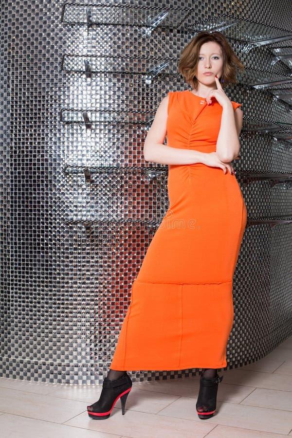 Het meisje in de oranje kleding en de zwarte schoenen royalty-vrije stock afbeeldingen