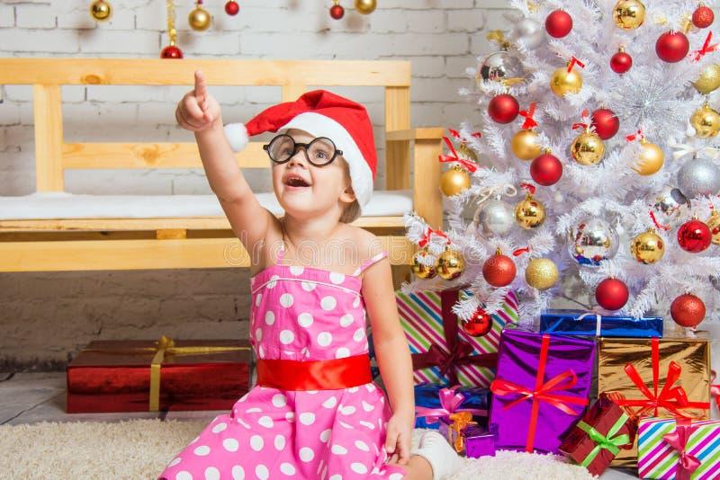 Het meisje in de rode hoed en de grappige ronde glazen richt een vinger op iets het interesseren royalty-vrije stock foto