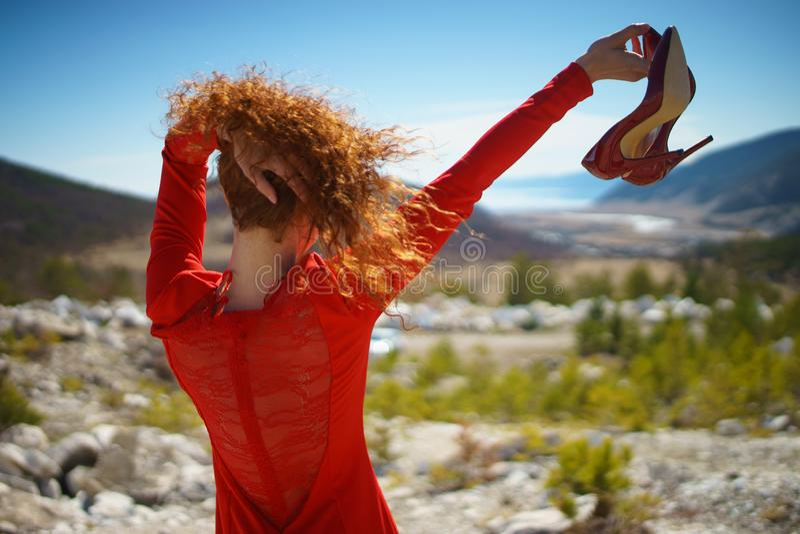 Het meisje in de rode kleding op de marmeren rotsbergen op de achtergrond royalty-vrije stock afbeelding