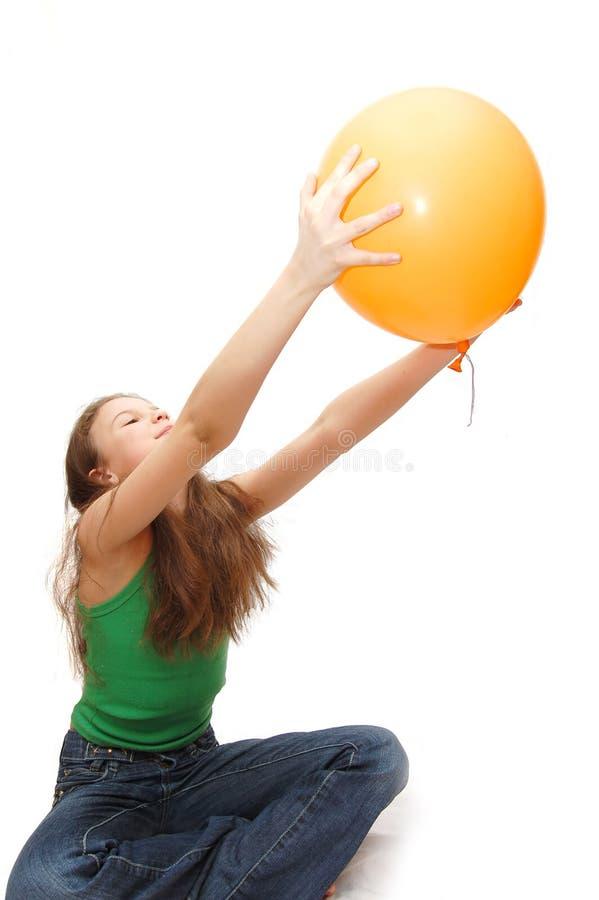Het meisje de tiener speelt met een ballon stock fotografie