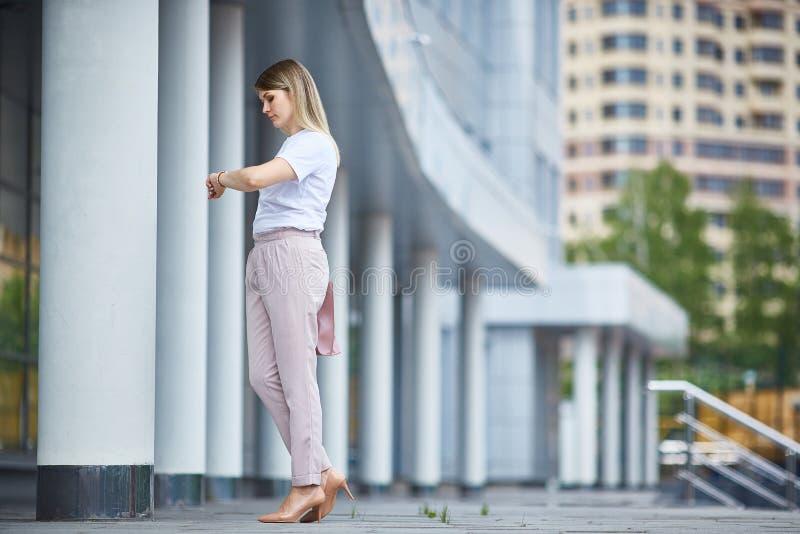 Het meisje in de volledige groei bekijkt het polshorloge dichtbij het bedrijfsgebouw stock afbeelding