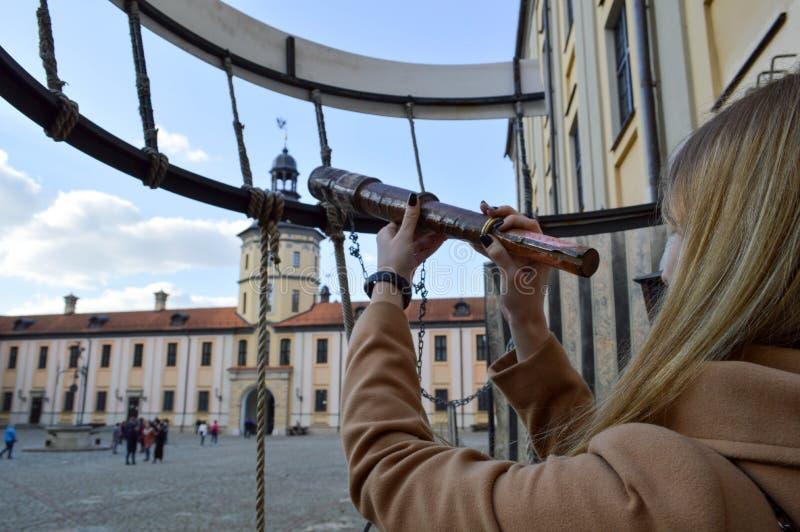 Het meisje, de vrouw kijkt in een oude oude telescoop op het Europese middeleeuwse toeristengebouw, het kasteel, het paleis met s stock afbeeldingen