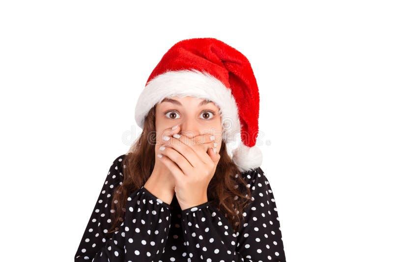 Het meisje deed schrikken en sluit de mond met haar handen emotioneel meisje in Kerstmishoed van de Kerstman dat op witte achterg royalty-vrije stock foto's