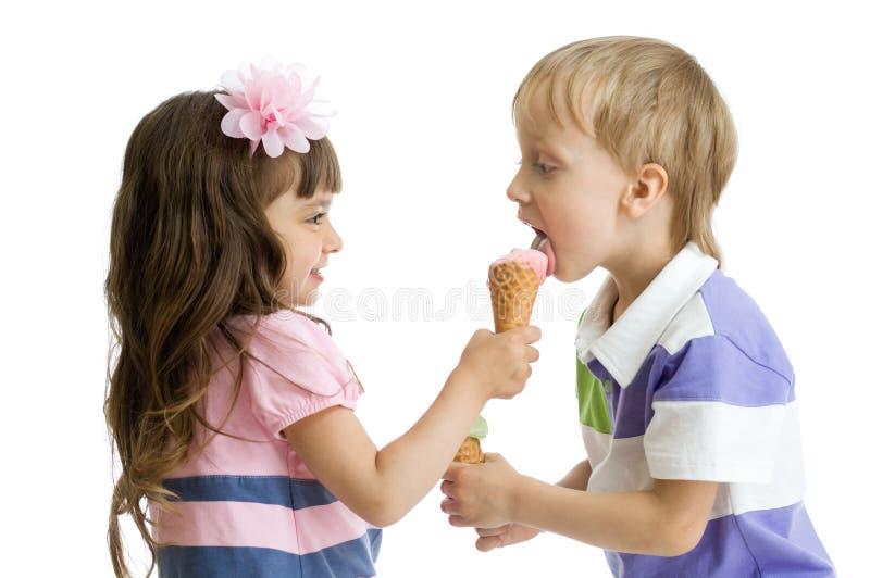 Het meisje deelt, geeft of voedt jongen met haar roomijs royalty-vrije stock foto's