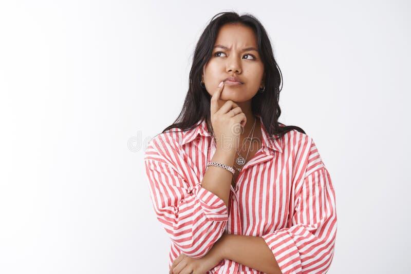 Het meisje denkt diep het hebben van veronderstellingen Portret van het nadenkende bepaalde ernstig-kijkt jonge wijze vrouw frons stock foto