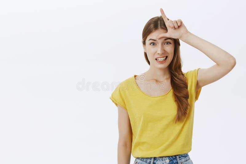 Het meisje denkt zij verliezer die geen geloof in eigen capaciteiten hebben Portret van somber onhandig knap wijfje in gele t-shi royalty-vrije stock afbeelding